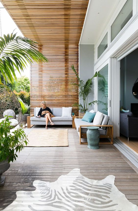 a contemporary sea terrace with sofas with neutral upholstery, rugs, pillows and potted plants is welcoming