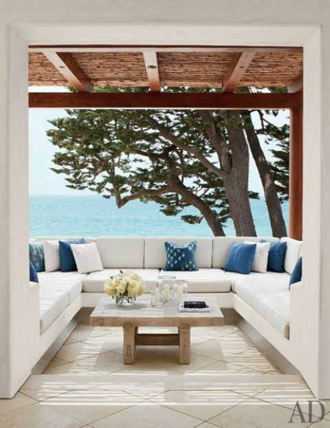 a contemporary seaside terrace with a U-shaped bench and blue and white pillows plus a gorgeous sea view