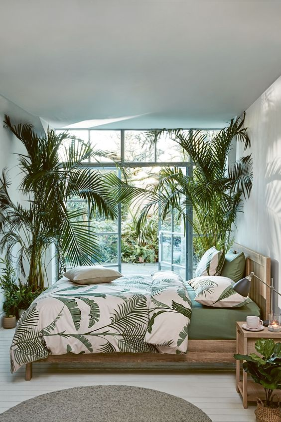 a contemporary tropical bedroom with light-stained wooden furniture, potted palm trees, tropical bedding