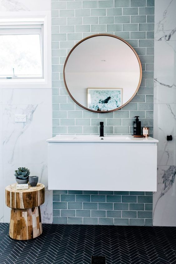 a contemporary sea inspired bathroom with light blue tiles, a black tile floor and a wooden tree stool