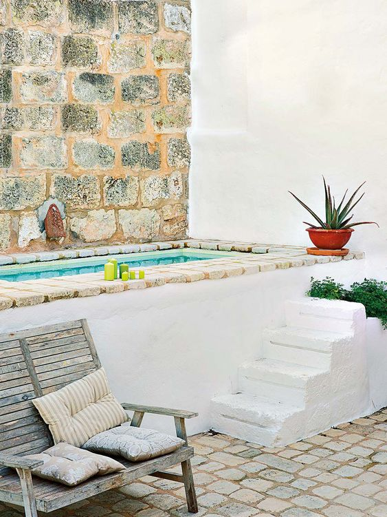 a cool Mediterranean outdoor bathroom with a stairs, planters, bricks and a shabby chic bench