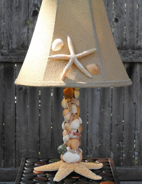 a cool table lamp of seashells covering the base, a starfish at the base and a neutral lampshade accented with a starfish