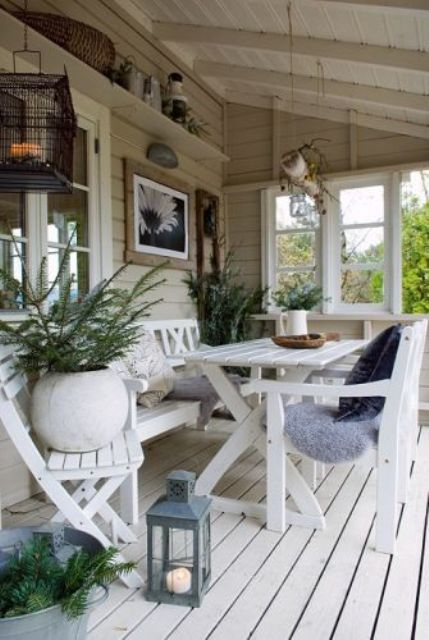 a covered beach patio with a white deck and white wooden furniture, potted plants, candle lanterns and some vintage stuff for decor
