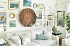 a cozy beach living room with white upholstered furniture, a large gallery walls with photos, artworks and a decorative basket