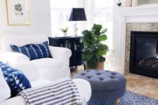 a cozy beach living space with white furniture, a blue ottoman, a printed rug and woven Roman shades