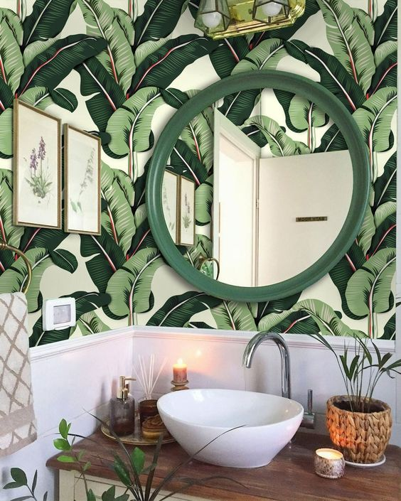 a cute modern tropical powder room with banana leaf wallpaper, a bowl sink, a green frame mirror, potted greenery