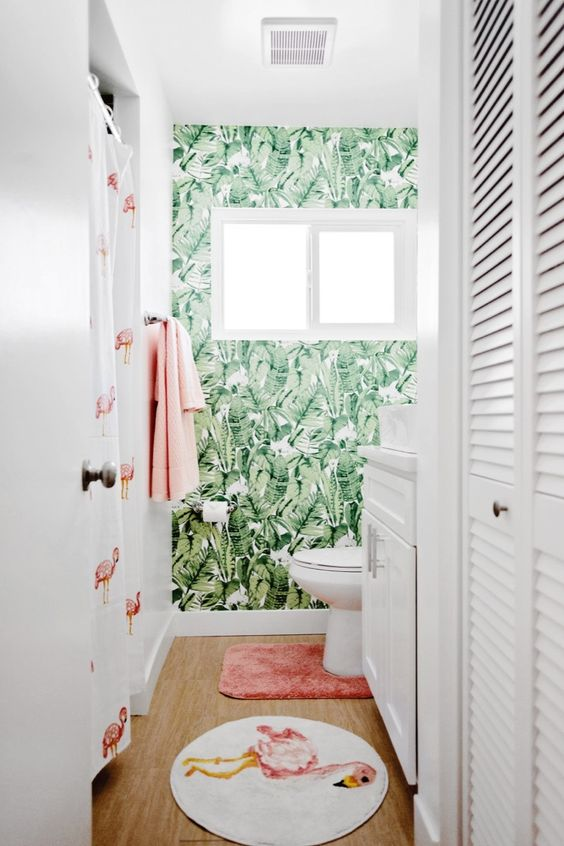 a fun and playful tropical bathroom with an accent wall, a pink and flamingo rug, a flamingo curtain and pink towels