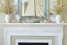 a fun beach mantel covered with net, some dried herbs in vases, corals, starfish, candles, birdies and a large boat in the center