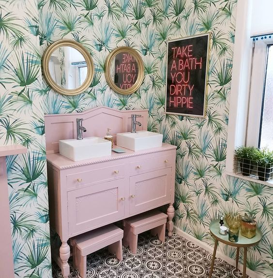 a funny tropical bathroom with tropical wallpaper, a light pink vanity and stools, a neon sign and touches of gold