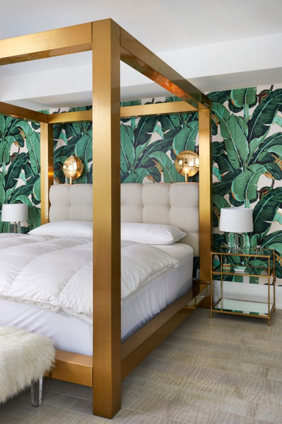a glam tropical bedroom with a statement tropical print wall, a large gold framed bed and gilded sconces