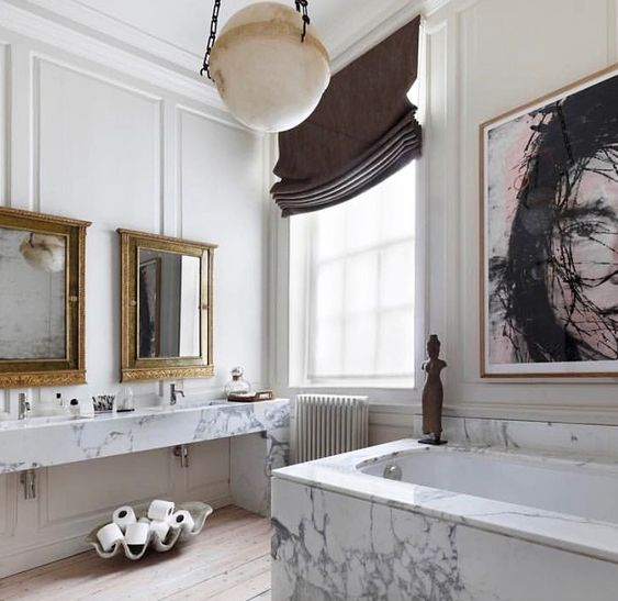 a gorgeous bathroom with a white marble vanity and tub, a statement artwork, mirrors in vintage frames and shades