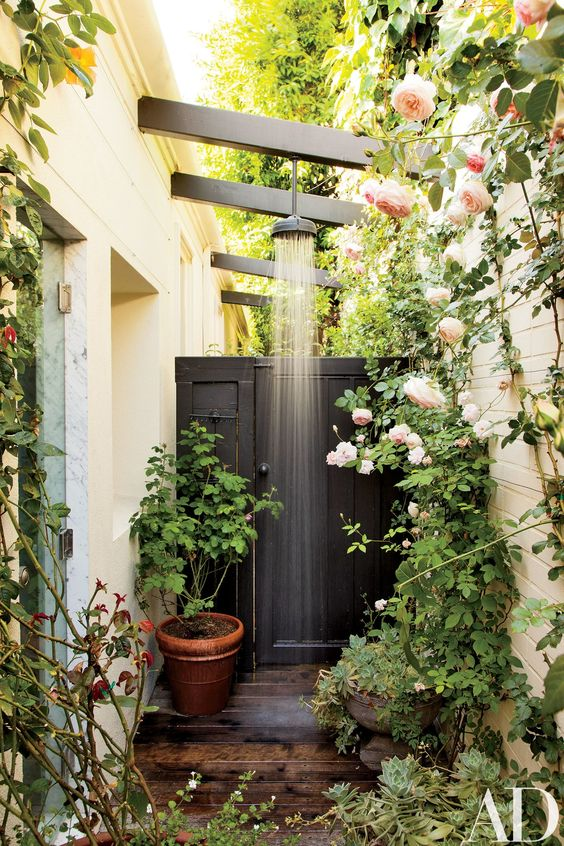 a gorgeous outdoor shower nook with potted and planted greenery and flowers and a shower itself