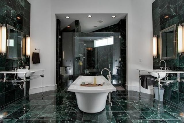 a gorgeously elegant bathroom with green marble tiles on the walls and floor and in the shower