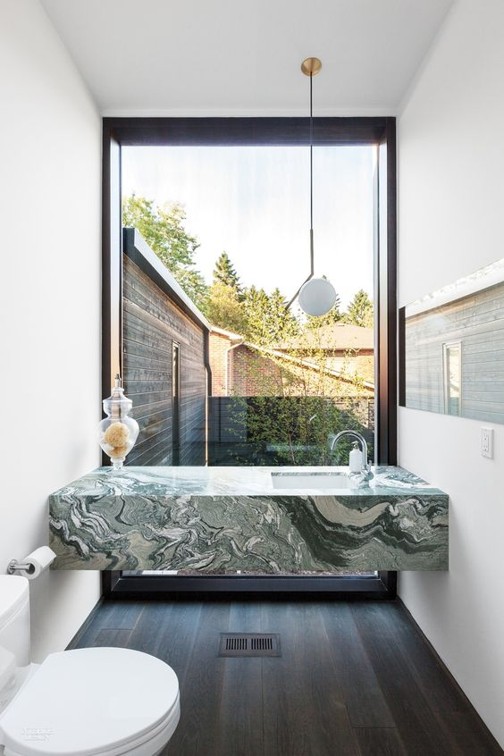 a green marble modern vanity in a small powder room with a view to the courtyard