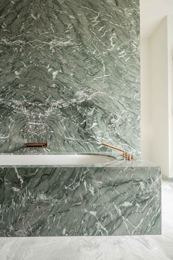 a green marble wall and a covered bathtub with brass fixtures create a really refined and luxurious space