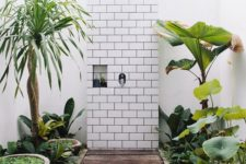 a jaw-dropping outdoor shower with lots of torpical greenery in pots and bowls and white subway tiles