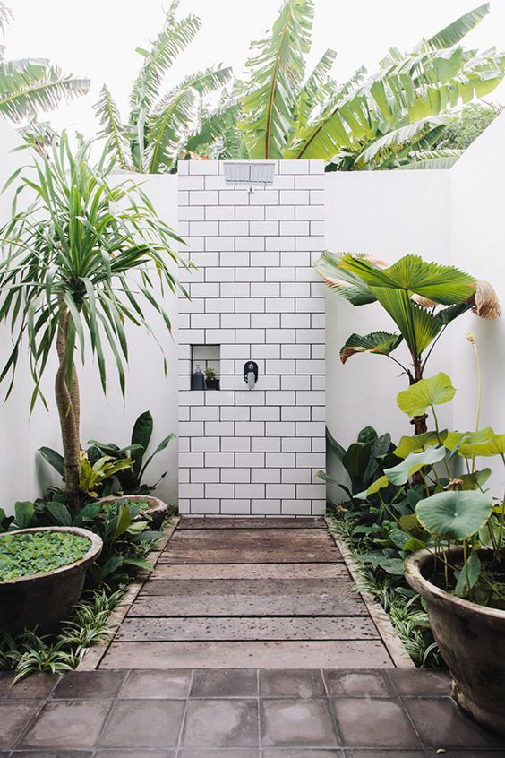 a jaw dropping outdoor shower with lots of torpical greenery in pots and bowls and white subway tiles