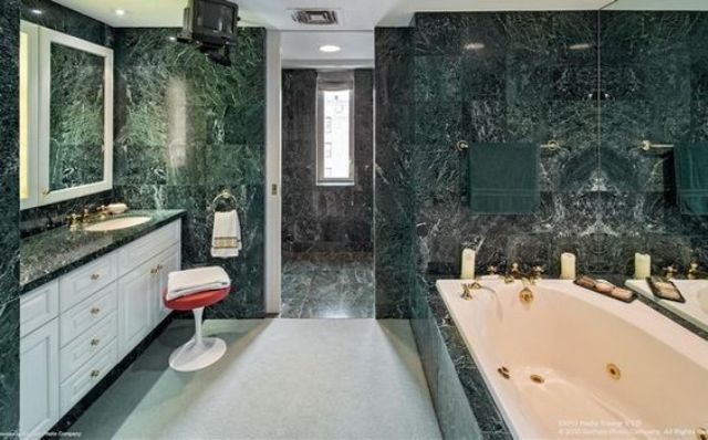a large modern bathroom clad with green marble tiles is made fresher with white furniture and cabinets