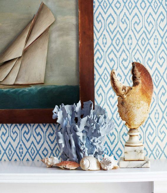 a lobster claw on a marble stand, a blue painted coral, seashells and a seaside artwork for a beachy mantel