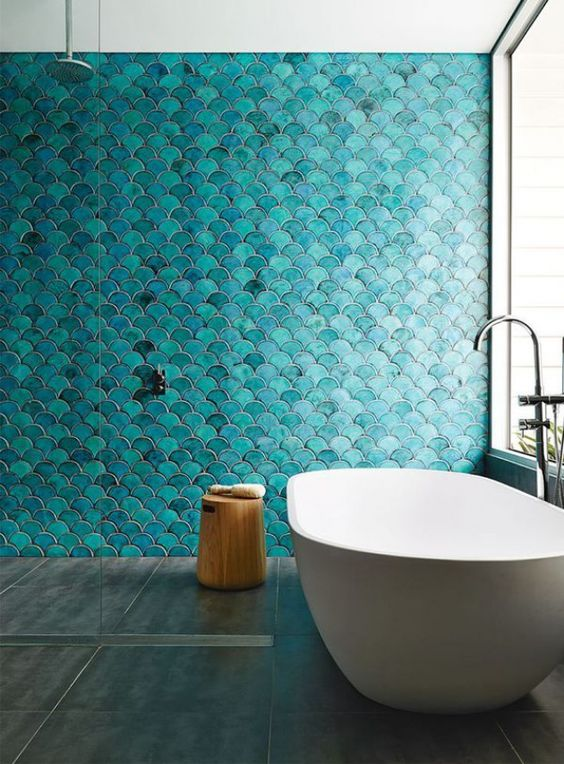 a minimalist bathroom inspired by the sea, with turquoise fish scale tiles and an oval bathtub
