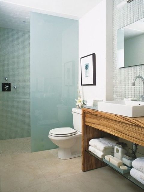 a minimalist beachy bathroom with aqua tiles in the shower, a frosted glass divider and light green tiles over the vanity