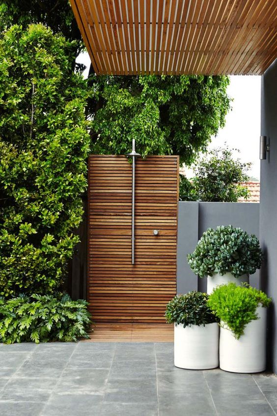 a minimalist outdoor shower with wooden plank screens, potted greenery and a shower