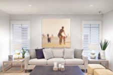 a modern beach living room in neutrals and navy, with printed piillows, jute square ottomans and an artwork