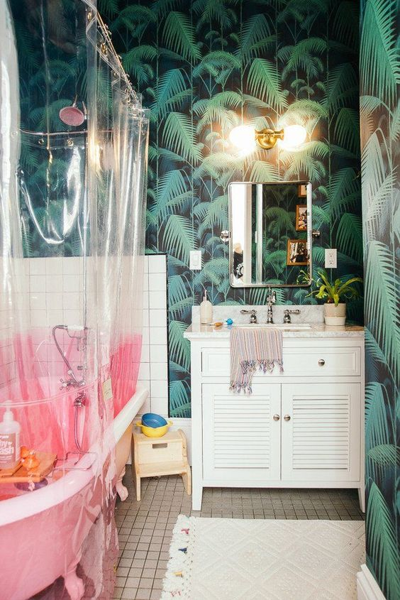 a modern bold tropical bathroom with dark tropical wallpaper, a pink clawfoot tub and a color block curtain, a vintage shutter vanity