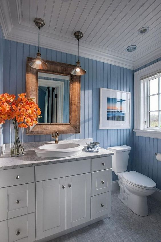 a modern sea-inspired bathroom with a white vanity, a wooden frame mirror, pendant lamps plus an artwork