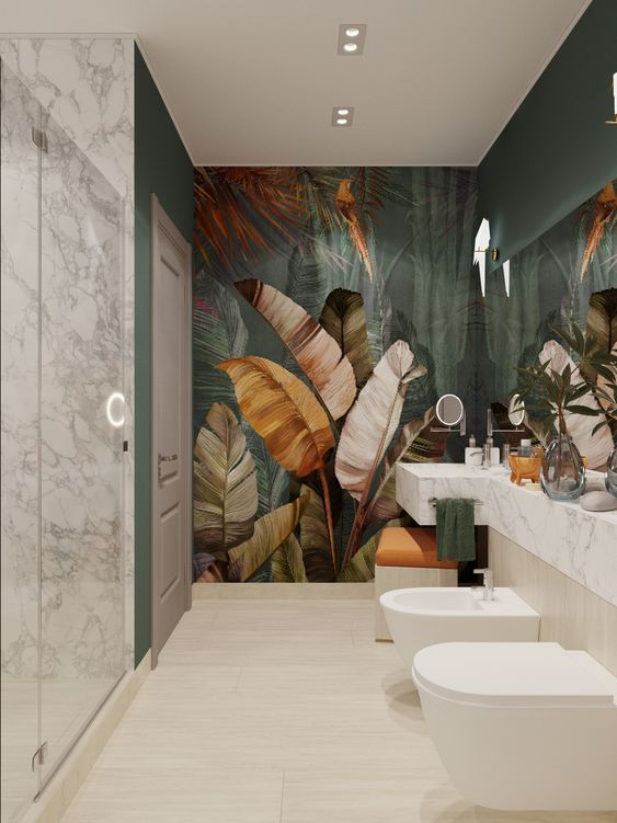 a modern tropical bathroom with a statement dark tropical mural, a marble vanity and shower plus built-in lights
