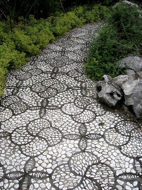 a monochromatic pebble garden path done with catchy floral-inspired patterns with black borders and white pebbles