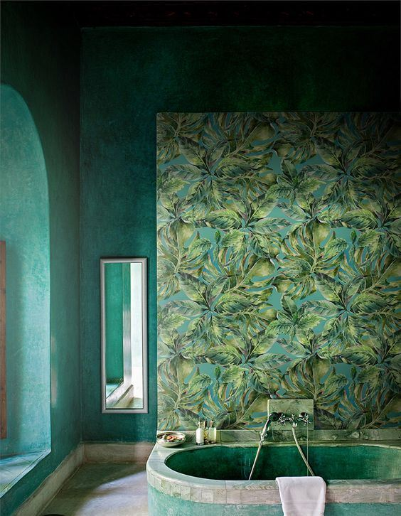 a moody tropical bathroom with a statement mural, a green plaster tub and grene plaster walls