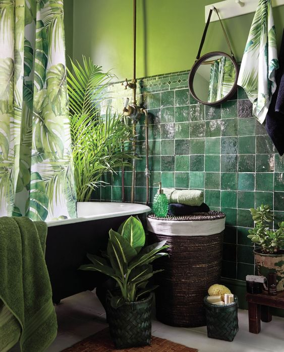 a moody tropical bathroom with green walls and dark green glossy tiles, a black tub, a woven stool, potted plants and tropical print textiles