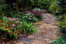 a natural and relaxed garden pathway with broken stones and pebbles plus bright blooms and greenery around