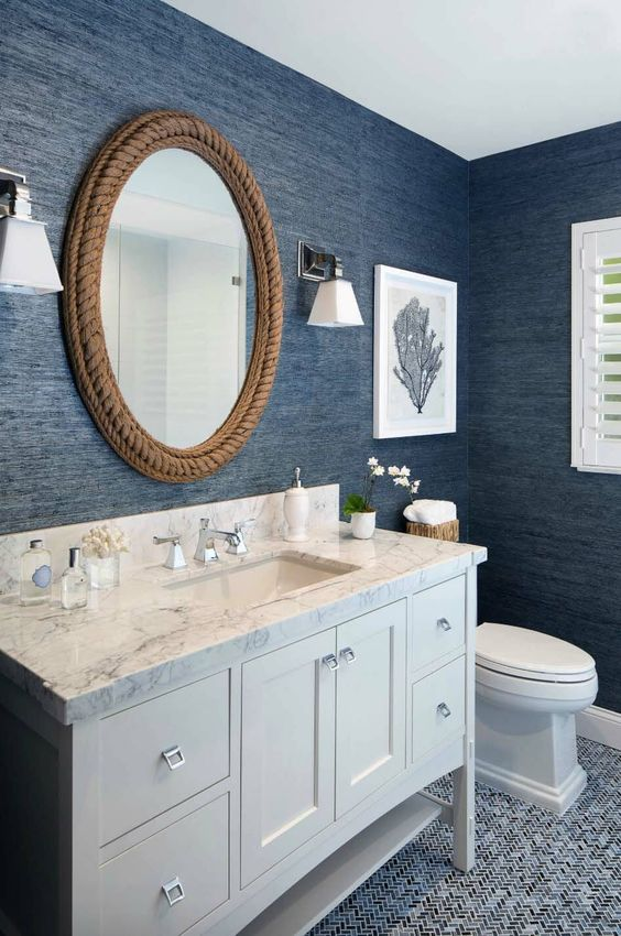 a nautical bathroom with navy textural wallpaper, a rope covered mirror and a white vanity plus artworks