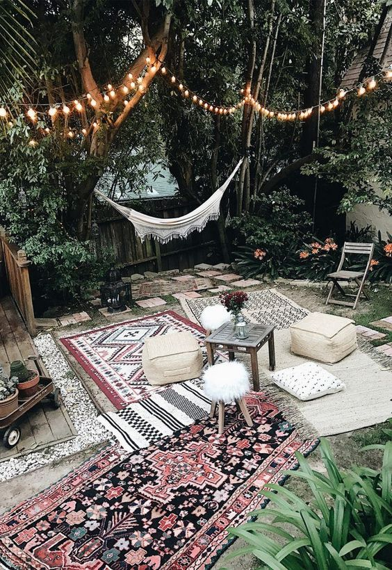 a neutral Moroccan patio done with a hammock, patterned boho rugs, leather ottomans and low furniture