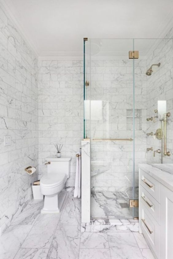 a neutral bathroom done with white marble tiles of various sizes and with brass hardware to spruce up the look