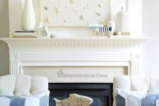 a neutral seaside mantel with white vases, little figurines, a beachy artwork with seashells, pebbles and starfish