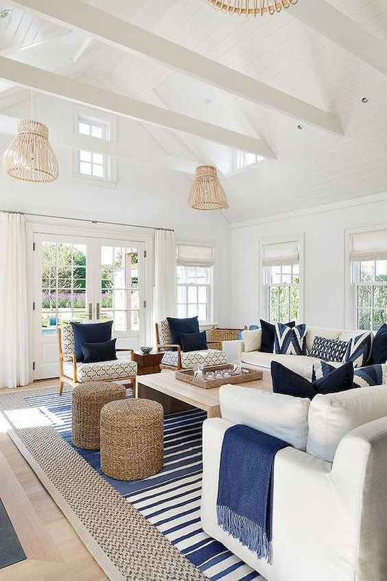 a preppy coastal living room with rattan lampshades, jute ottomans, stripes and traditional furniture