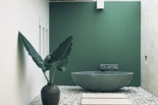 a refined minimalist outdoor bathroom with a green statement wall and bathtub, pebbles, stone tiles and a large vase