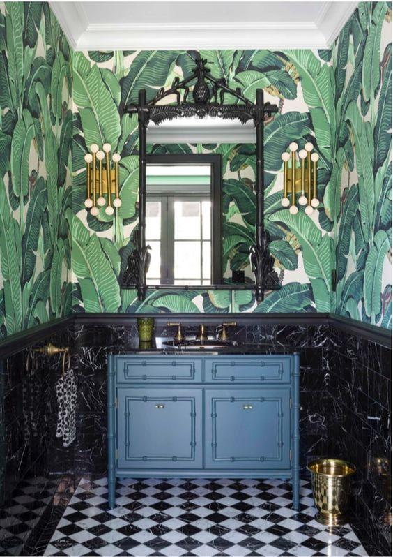 a refined vintage tropical bathroom with banana leaf wallpaper, black marble tiles, a navy vanity and touches of gold