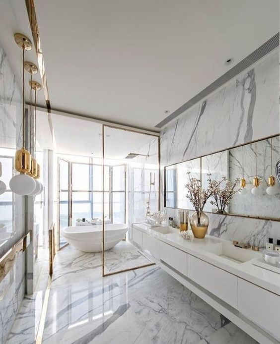 a refined white marble bathroom with a glazed wall, a tub, a mirror and pendant lamps and a floating vanity