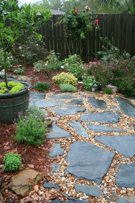 a relaxed and all-natural garden path with pebbles and rough dark stones of various shapes and looks