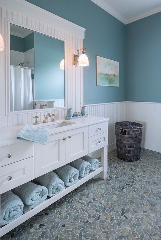 a sea farmhouse bathroom with a large white vanity and a mirror, blue walls and light blue towels and touches