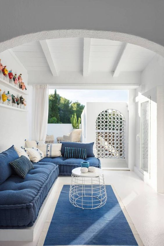 a seaside blue and white patio with modern furniture and pillows, a metal table, a blue rug and colorful accessories