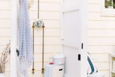 a seaside inspired outdoor shower with vintage white doors, wood and striped towels in blue