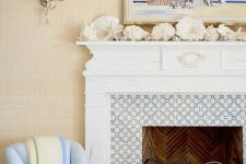 a seaside mantel with corals, starfish, seashells, driftwood and a bright beachy artwork over the mantel