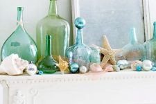 a seaside mantel with seashells, blue and pearl ornaments, blue and green bottles, starfish and beads is lovely