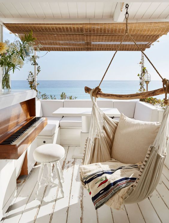 a seaside terrace with a wooden deck, a hanging chair, a sofa, a piano and a cool sea view is amazing