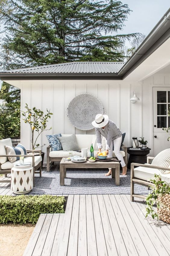a seaside terrace with a wooden deck and light stained wooden furniture, neutral upholstery, greenery and a black and white decorative plate